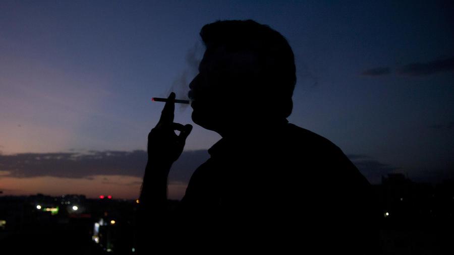 Un hombre fumando en mayo en India.