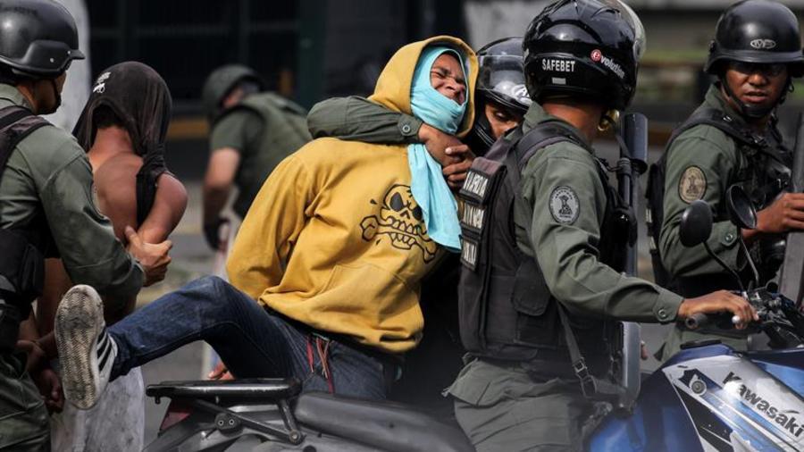 La Guardia Nacional Bolivariana (GNB) aprehende a un manifestante durante enfrentamientos contra opositores este jueves 27 de julio de 2017.