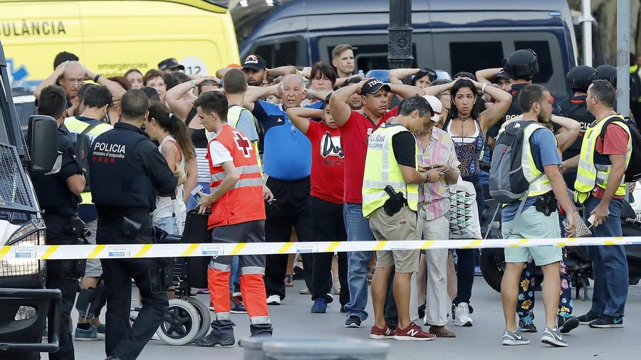 Un grupo de gente con los brazos en alto ante el despliegue policial en el lugar del atentado ocurrido hoy en las Ramblas de Barcelona