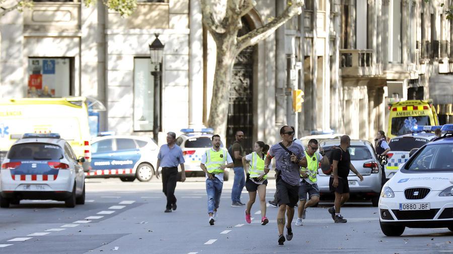 Gente en el lugar en el que una furgoneta ha atropellado esta tarde a varias personas que paseaban por las Ramblas de Barcelona.