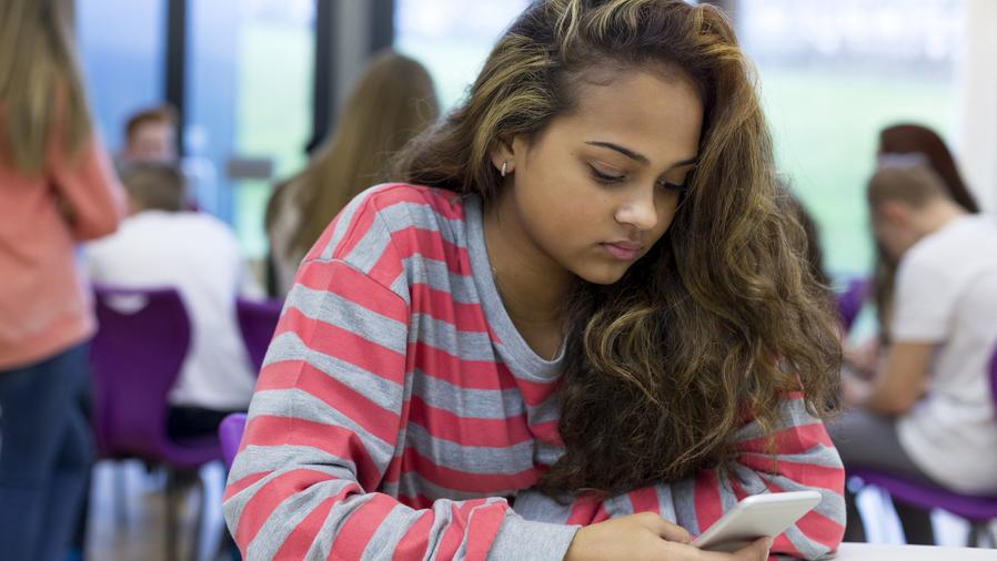 Niña usando teléfono móvil en la escuela