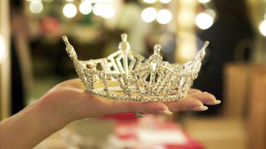 Mano sosteniendo una corona