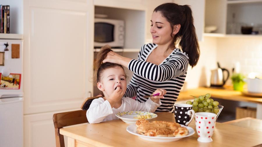 Madre preparando a su hija para la escuela