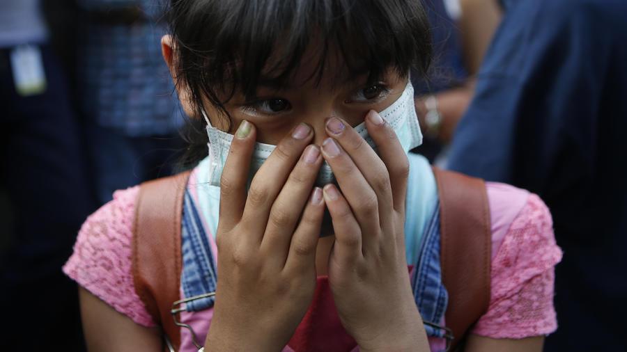 Una joven protegida con una máscara observa los trabajos de rescate en la Ciudad de México el viernes.