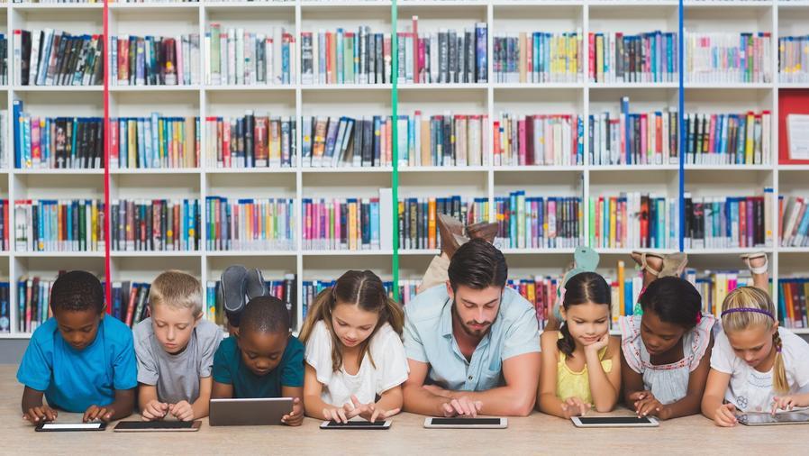 Profesor y niños en el piso usando tabletas