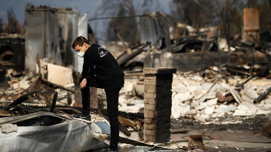 Un agente en medio de los resto de una vivienda arrasada por fuegos en California