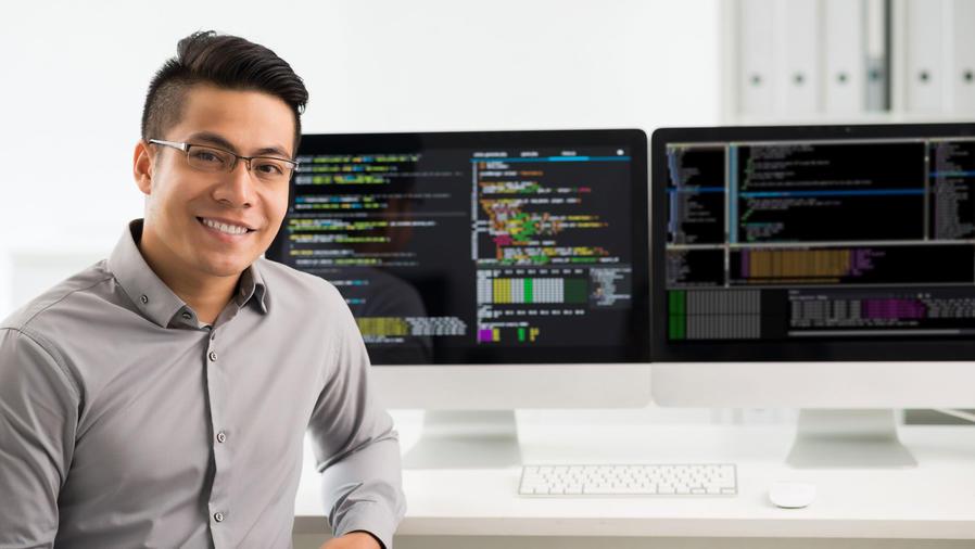 Hombre frente a monitores de computadoras