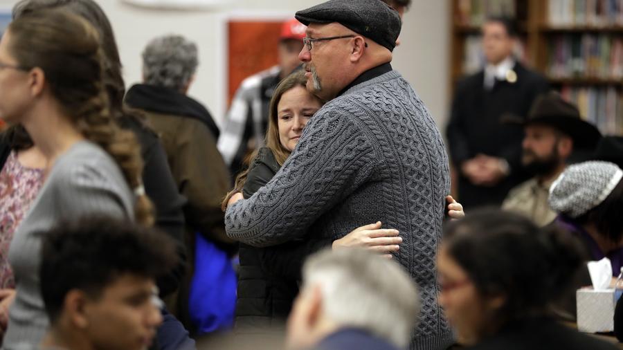 Frank Pomeroy, el pastor de la Primera Iglesa Baptista, abra a una mujer que también perdió un familiar en la masacre de Texas.