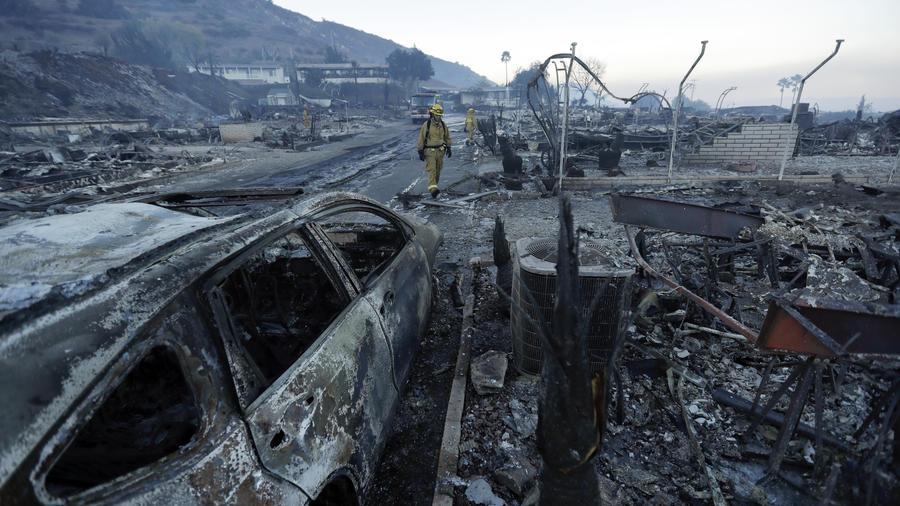 Bomberos examinan las casas que quedaron destruidas por los incendios forestales en Fallbrook, California.