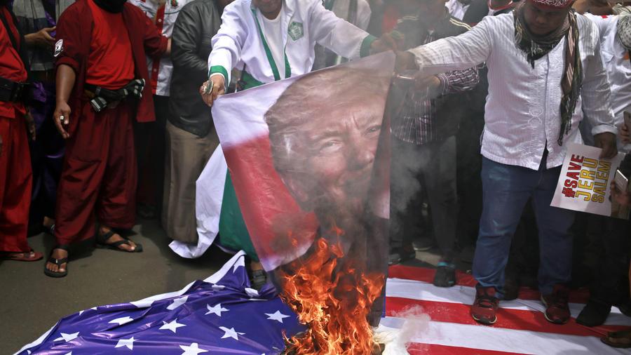 Manifestantes queman un cartel con la imagen de Trump, durante una protesta en el exterior de la embajada de Estados Unidos en Yakarta, Indonesia.