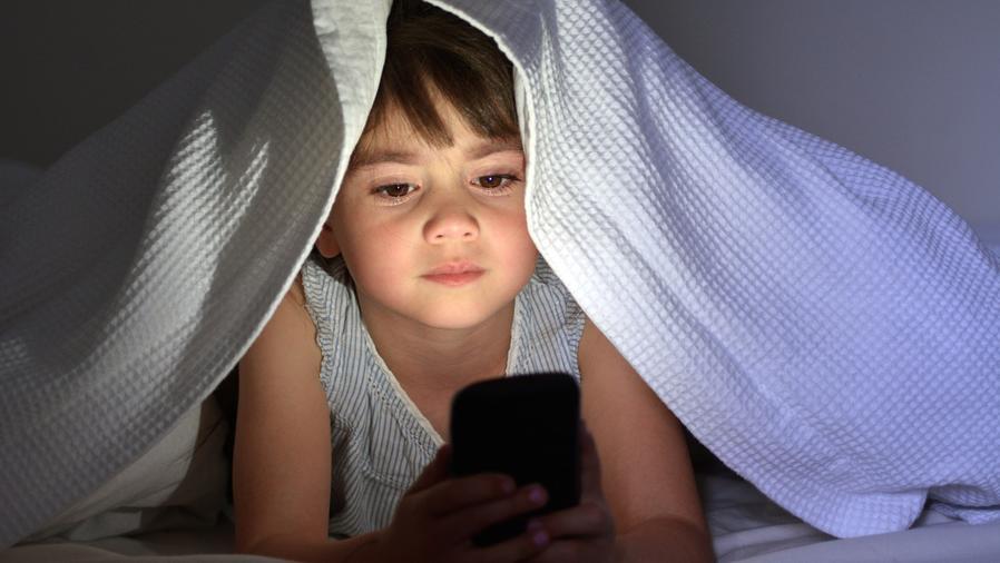 Niña en la cama usando teléfono móvil