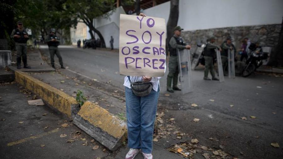 """Una mujer sostiene un cartel en el que se lee """"Yo soy Óscar Pérez"""" junto a miembros de la Guardia Nacional Bolivariana y la Policía Nacional Bolivariana que custodian las inmediaciones de la morgue en donde está cuerpo del exagente Pérez el miércoles 17 d"""