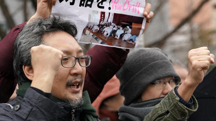 Manifestantes gritan consignas fuera del lugar de un simulacro de evacuación simulando un ataque con misiles balísticos de Corea del Norte en Tokio, el lunes 22 de enero de 2018.