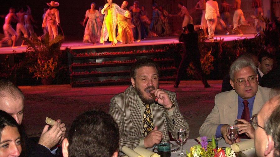 """""""Fidelito"""", al centro, se fuma un cigarro durante la apertura del festival internacional de cigarros en 2002."""