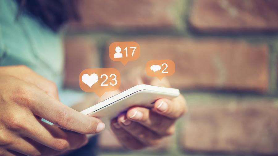 Mujer con teléfono y notificaciones de redes sociales