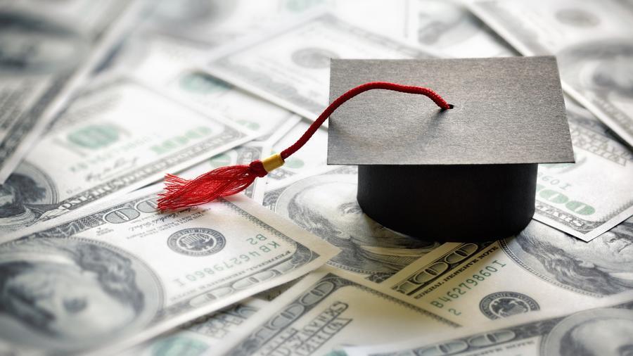Gorro de graduación sobre billetes
