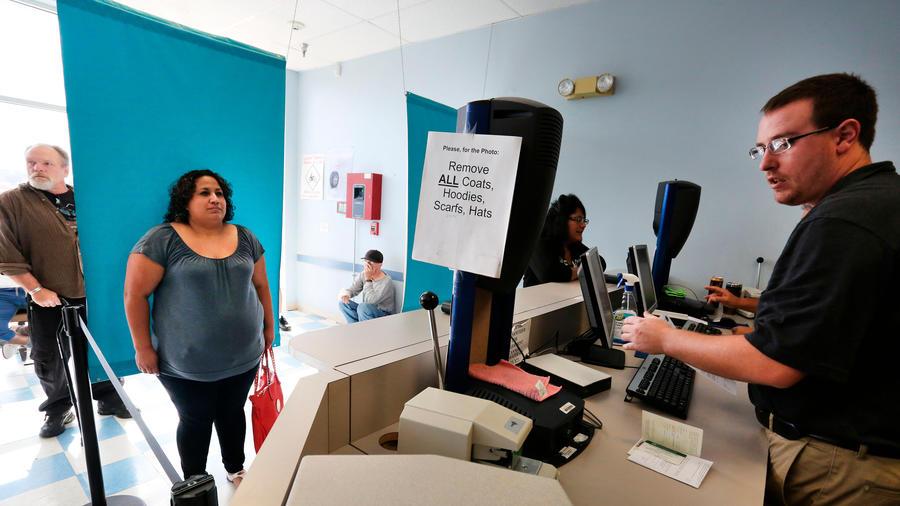 En esta fotografía del 1 de agosto de 2014, se muestra a la inmigrante Rosalva Mireles mientras le toman una foto para tramitar su licencia de conducir.