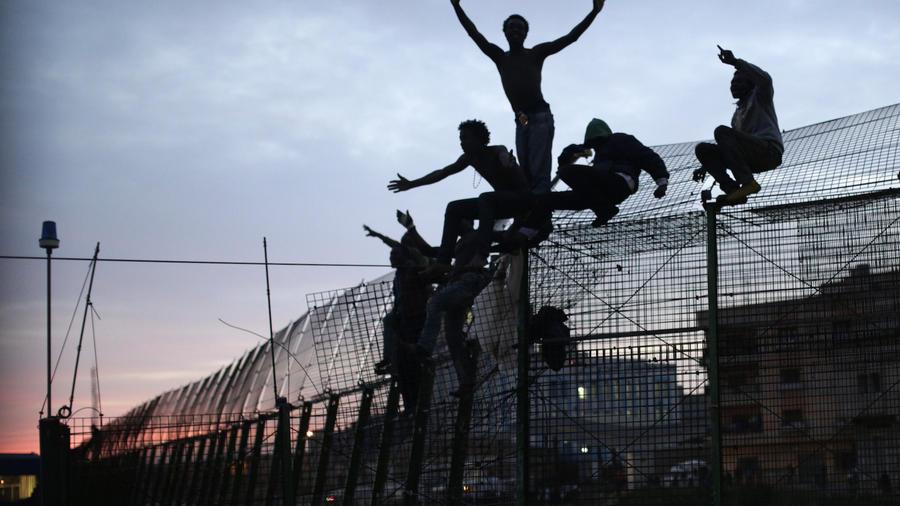 Inmigrantes subidos a la valla de la frontera española, en marzo de 2014.