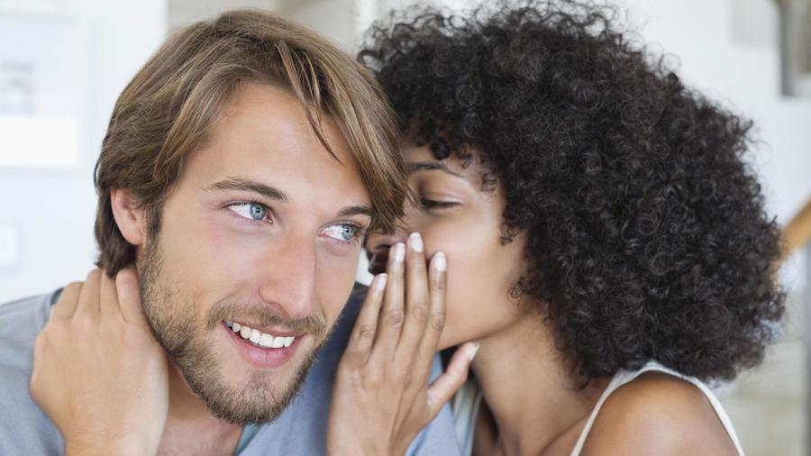 Mujer susurrando al oído a un hombre