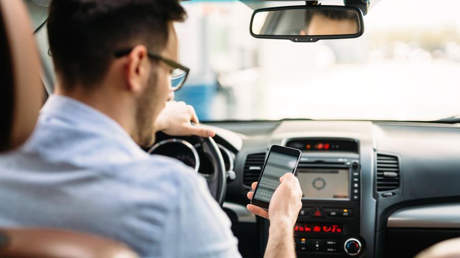 Hombre en su carro usando teléfono móvil