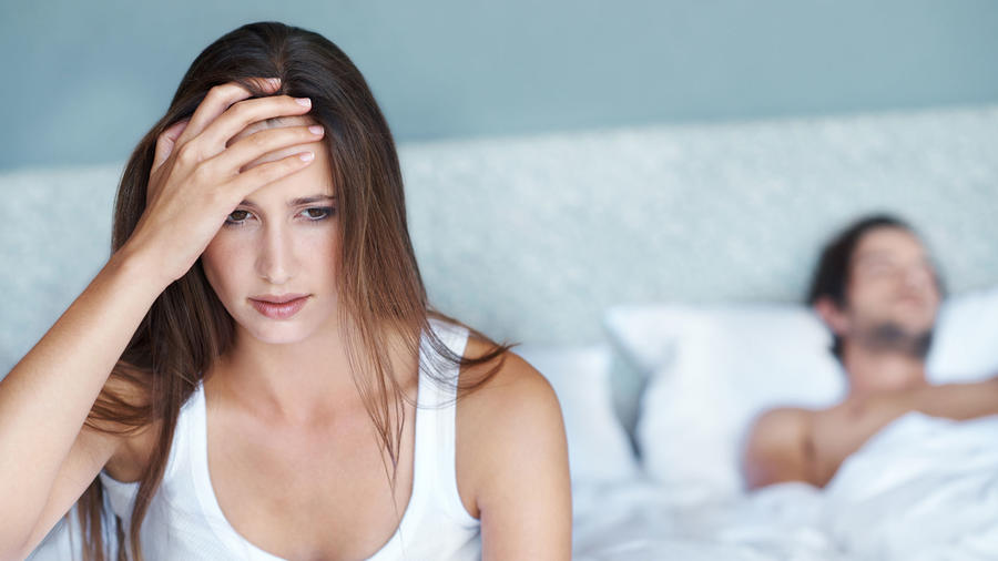 Mujer preocupada en la cama con su pareja