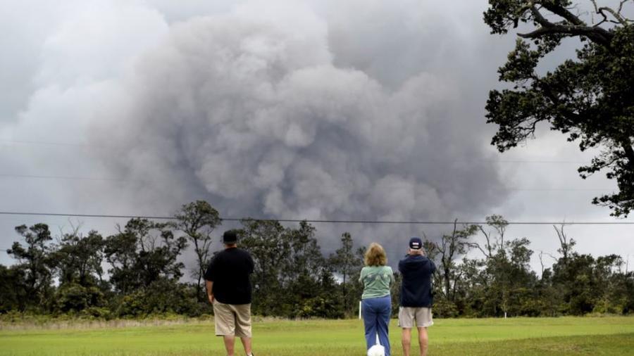 Los vecinos observan la columna de ceniza del volcán en erupción.
