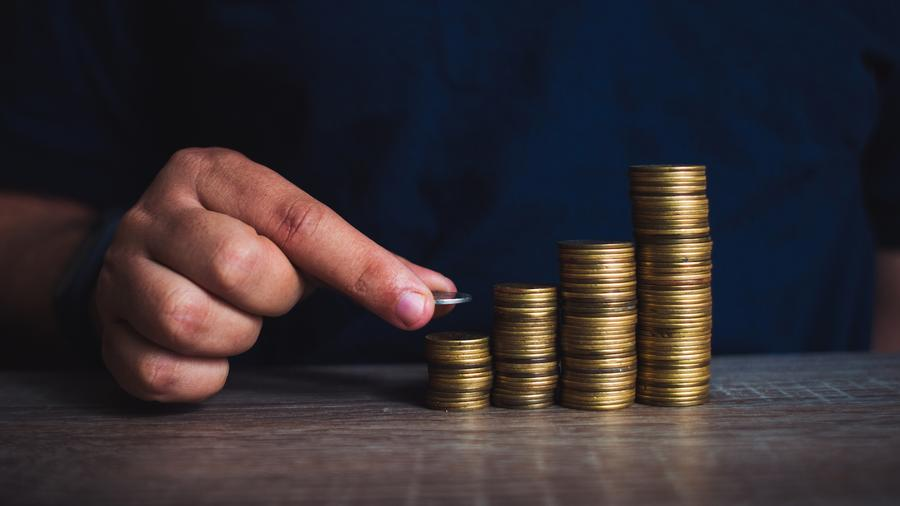 Persona juntando monedas en pilones