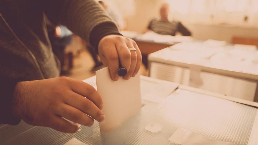Manos de persona insertando voto en urna