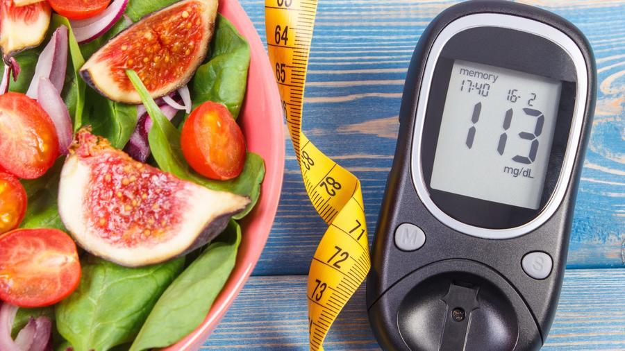 Ensalada, cinta métrica y medidor de glucosa