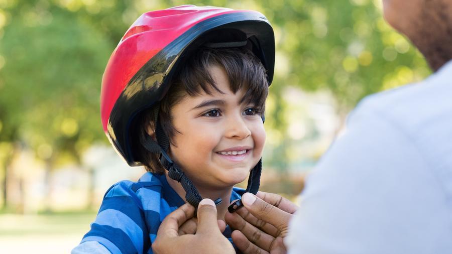 Padre atando casco de su hijo pequeño