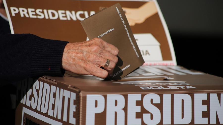 Una persona introduce su voto en una urna en México el 1 de julio de 2018