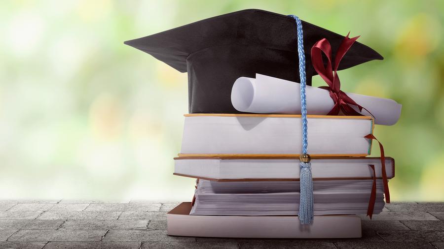 Libros universitarios y birrete de graduación