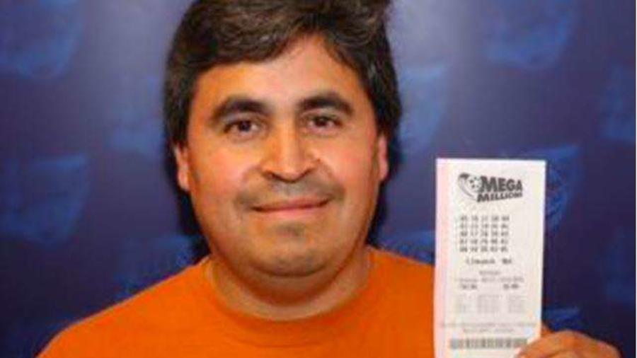 Hombre con un billete de la lotería Mega Millions de EEUU en sus manos