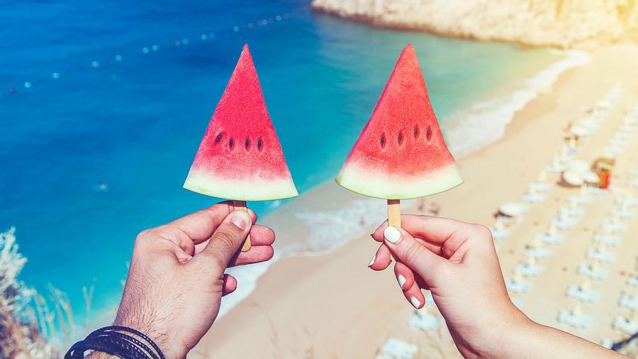 Pareja sostiene palillos con sandía, en la playa