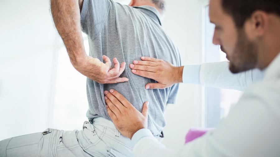 Médico revisando a hombre de espaldas