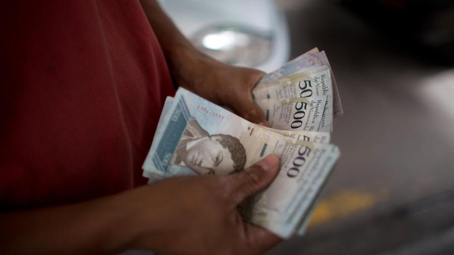 Un empleado cuenta billetes de bolívares en una gasolinera en Venezuela en una imagen de archivo