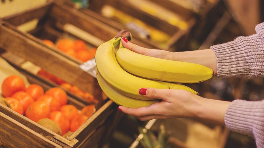 Mujer eligiendo bananas en la tienda