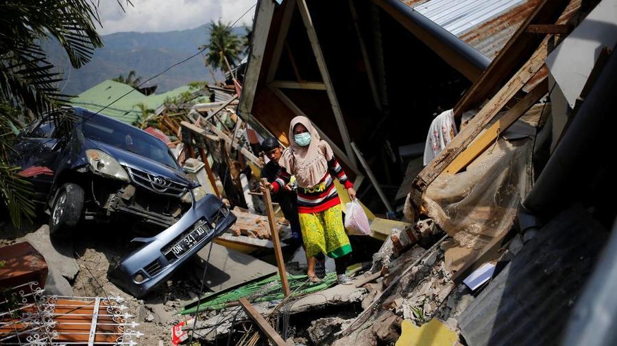 Una mujer se abre paso entre los escombros este martes en el barrio de Balaroa en Palu.
