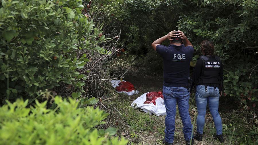 Forenses observeanrestos humanos exhumados de una fosa clandestina en el estado de Veracruz