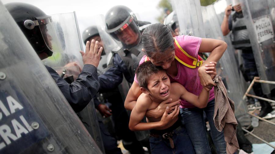 Inmigrantes hondureños, rodeados de policías en la frontera mexicana este viernes.