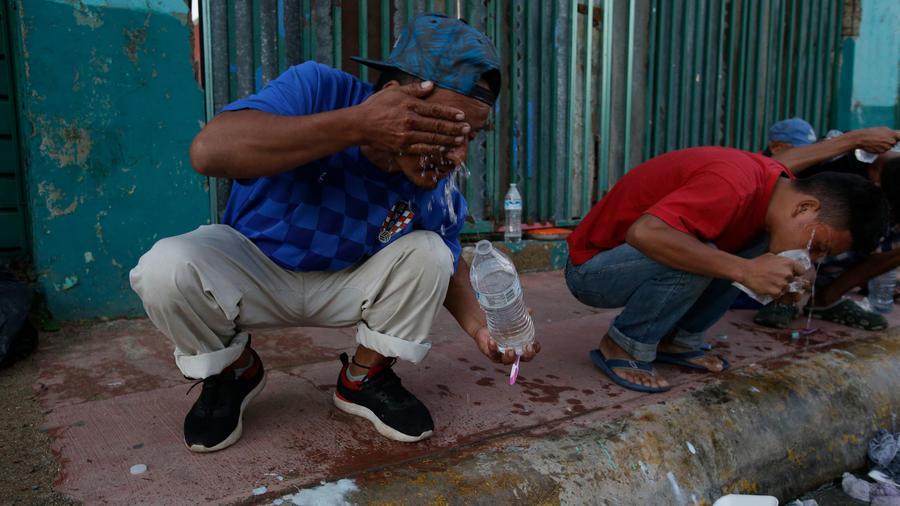 Dos integrantes de la caravana se asean hoy en Huixtla en México
