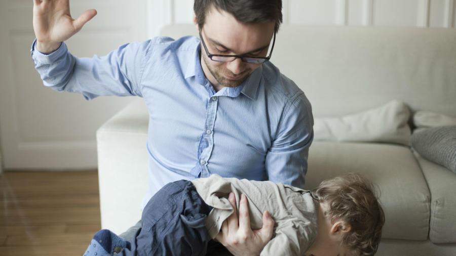 Padre azotando a su hijo