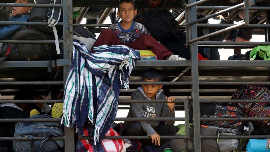 Migrantes centroamericanos, parte de la caravana que espera llegar a la frontera con Estados Unidos, viajan este domingo en un camión en Celaya, México.