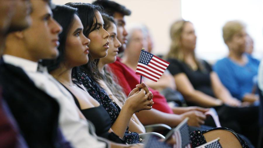 Los nuevos ciudadanos de Estados Unidos sostienen la bandera del país durante una ceremonia de naturalización.