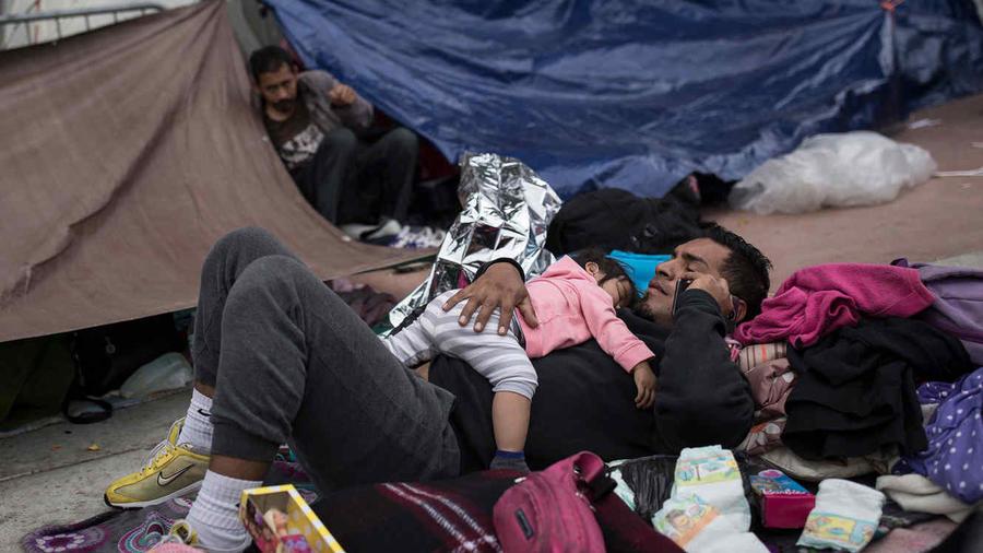 Un hombre con una niña en sus brazos de la caravana de inmigrantes en la frontera con EEUU.