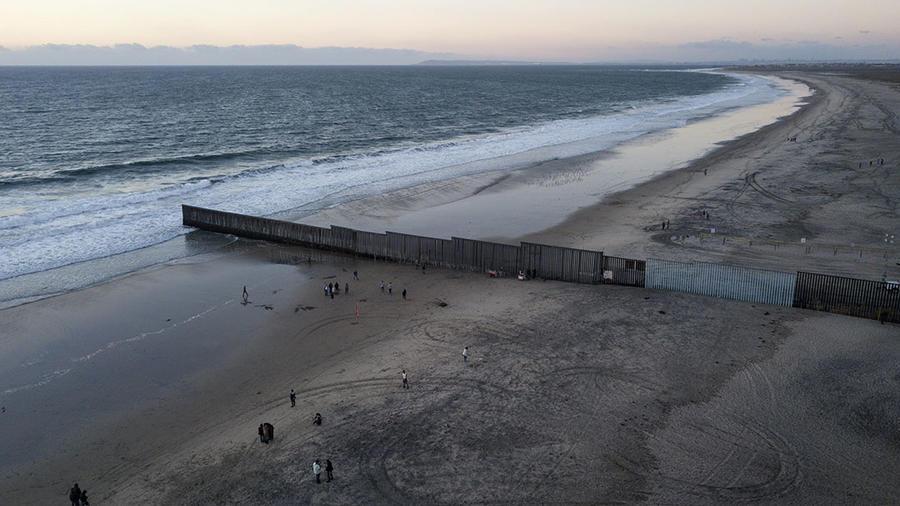 Varias personas caminan cerca de la barda que separa a México y Estados Unidos en la ciudad fronteriza de Tijuana.