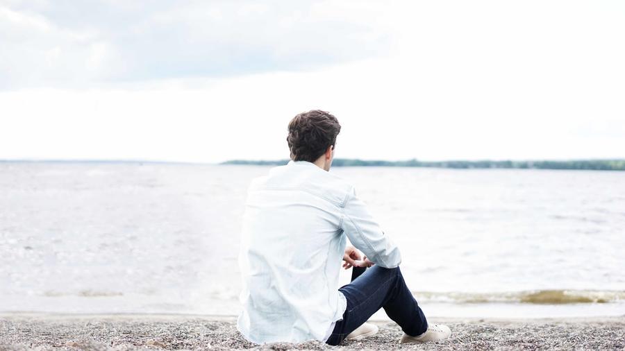 Hombre sentado frente al mar