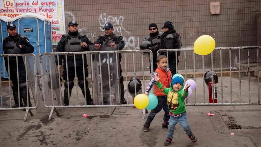 Niños de la primera caravana migrante juegan frente a agentes policiales en Tijuana, México