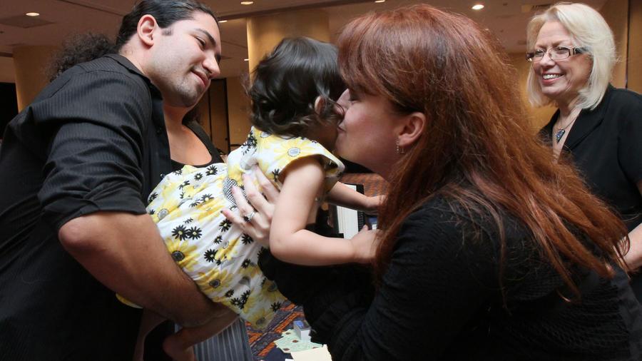 Sherrilyn Kenyon besa a una bebé durante un encuentro de escritores en Nueva York en 2011.