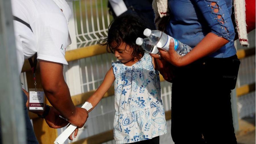 Autoridades mexicanas colocan este jueves un brazalete a un niño migrante hondureño para que pueda ingresar al territorio mexicano.